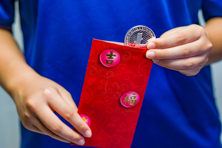 A close up of a girl removing a Litecoin coin from a traditional red packet. Stock Photo