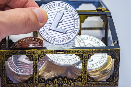 Close up of a hand picking out a Litecoin coin from a treasure chest.