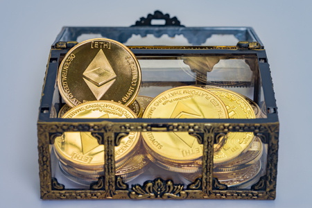 A treasure chest full of golden Etherium coins on a clean background Stock Photo
