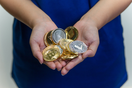 A young girl with a bunch of crypto currency coins cupped in both hands.