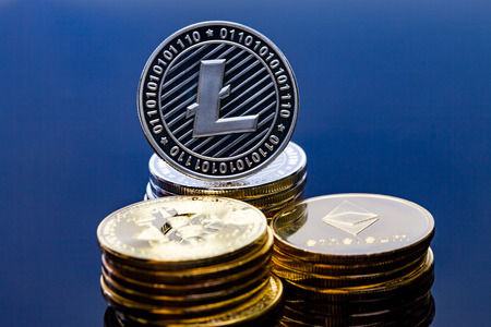 A single litecoin coin on top of a pile of crypto currency.