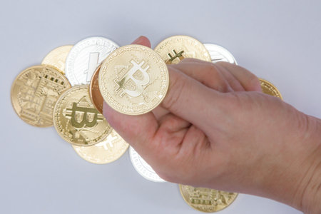 Close up of a hand about to flip a Bitcoin coin