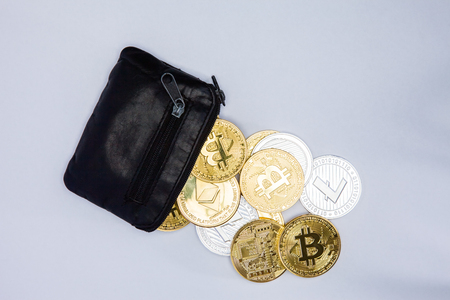 A black coin purse spilling out crypto currency coins