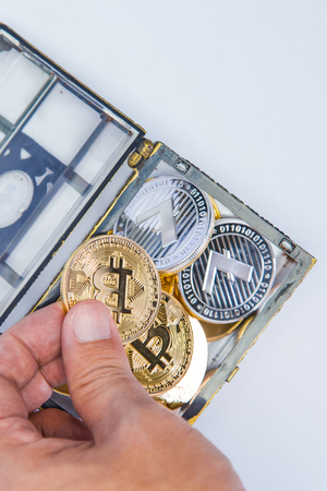 A treasure chest full of crypto currency coins on a clean background Stock Photo