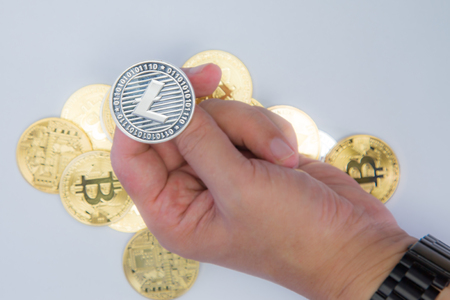 Close up of a hand about to flip a Litecoin coin Stock Photo