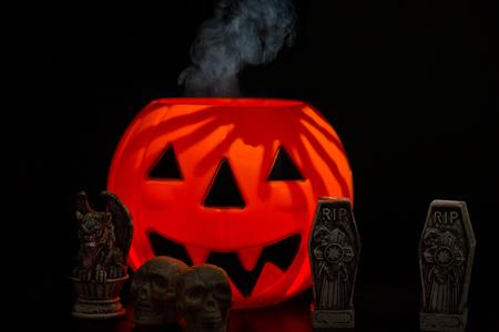 Halloween night scene with Jack O Lanterns, smoke, tombstones, skulls and gargoyles