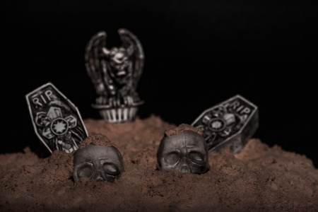 Halloween night graveyard scene with tombstones, skulls and gargoyles