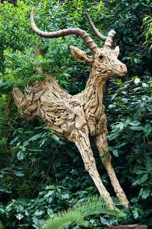 A wooden gazelle statue made up of small pieces of wood hops out of the forest. Editorial