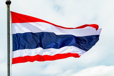 Close up of the Thai flag on a pole, waving.
