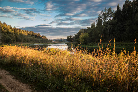 windless: autumn grass near the river lit by the setting sun, windless weather, calm water and sky with beautiful clouds