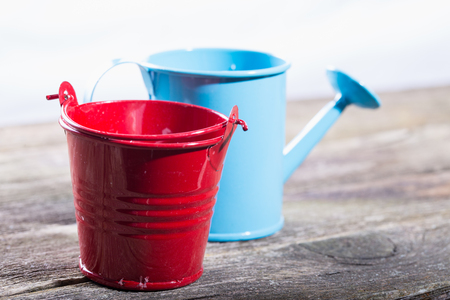Garden bucket and watering can on old gray boards. Small depth of sharpness
