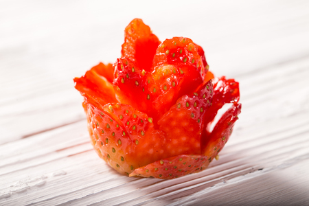 The flower which is cut out from strawberry berry on a white board. Close up, small depth of sharpness
