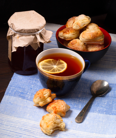 Cup of tea, home-made cookies and jar of jam. On a napkin from fabric, a dark background, a close up Stock Photo