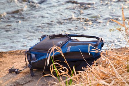 The backpack lies on a stone against water flow. The dry grass in the foreground, a backpack of blue color, a scene is lit with the sunset sun