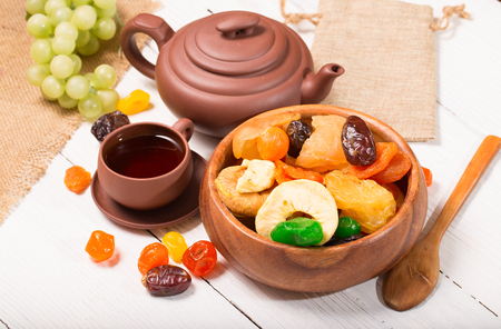 Tea drinking with dried fruit from pottery. Rural style, close up, small depth of sharpness Stock Photo