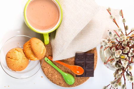 Breakfast: cocoa, cakes, willow branches. And also a chocolate bar and teaspoons on a support from a stopper. Top view, white background Stock Photo