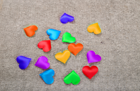 Sprectrum multi-colored hearts on a gray background. A scattering of hearts from fabric of all colors of the rainbow on a gray stone surface Stock Photo