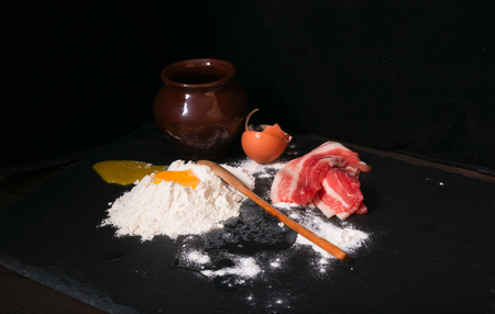 broken hill: Crude products on a kitchen table. Crude bacon, the broken egg and flour. On a background a clay ceramic pot, on a flour hill a wooden spoon. Products against a dark background