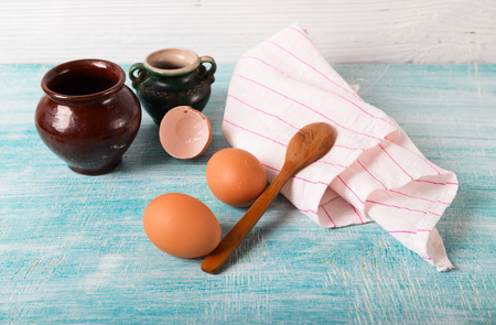 Clay pots, eggs and towel. A table fragment in kitchen. A blue wooden table-top, on a towel a wooden spoon Stock Photo