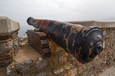 Ancient guns on a fortress wall. Guns are covered with a rust, zakroyeplena of hectare stone walls Stock Photo