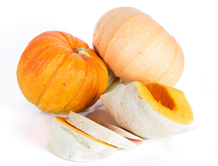 Two whole pumpkins and pieces of pumpkin  on a white background. A close up, small depth of sharpness, At the cut pumpkin orange pulp