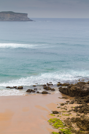 View of the sandy beach in cloudy foggy day. Spain, suburb of Suances, summer day in the Province of Cantabria, it is photographed from Playa de Los Locos.
