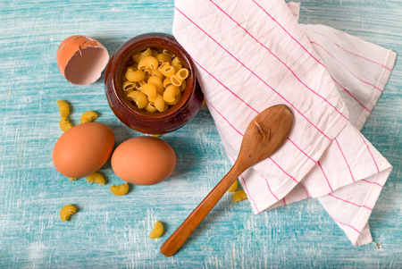Ceramic pot with macaroni and several eggs. Top view. Nearby the wooden spoon and a towel, on a blue wooden table in rural style lies