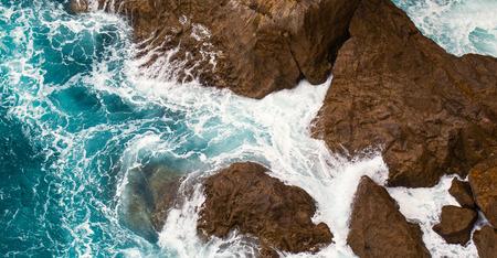 Foamy surf at rocks. The top view, sea waves foam at big coastal stones