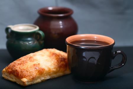 Dark ceramic ware and pie. Close up, dark background, small depth of sharpness Stock Photo