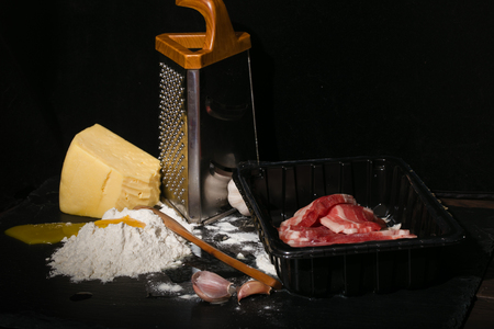 broken hill: Crude products on a kitchen table. Crude bacon, the broken egg and flour. On a background a grater and cheese, on a flour hill a wooden spoon. Products against a dark background