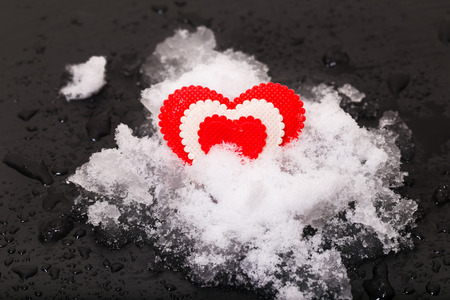 Heart on snow. Snow lies on a black background, a close up, water drops from the melted snow Stock Photo