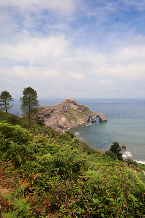 northern spain: View from the coast on the rock in the ocean with a chapel Doniene Gaztelugatxeko. A chapel Doniene Gaztelugatxeko chapel (San Juan - Gastelugache) in the Basque Country, northern Spain, in the sunny summer day against the blue sky with plumose clouds Stock Photo