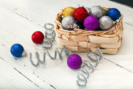 Wattled basket with Christmas decorations. Multi-colored spheres and brilliant tinsel. Close up, small depth of sharpness