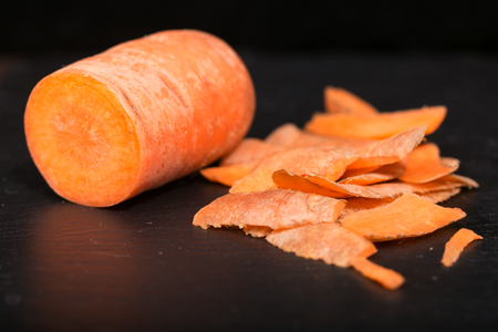 Carrots and carrot cleanings on a black board. Close up, small depth of sharpness