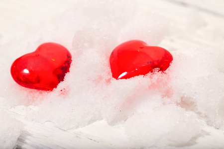 Two glass hearts on snow. Snow lies on a light background, a close up