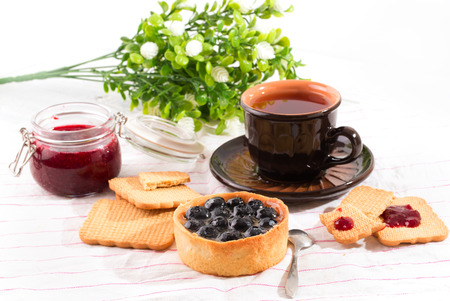 papaver: Breakfast with bilberry cake. Bilberry cake, cookies and a cup with tea on a light table. Flowers on a background