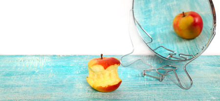 distort: Bit of apple and reflection in a mirror of the whole apple. The taken a bite apple is reflected in a blue colored table as whole. At the left above empty seat white