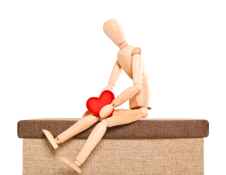 marioneta de madera: The sad person holds heart in hand. The doll, a wooden dummy sits holds in hand heart from red fabric. The pose of the person expresses grief