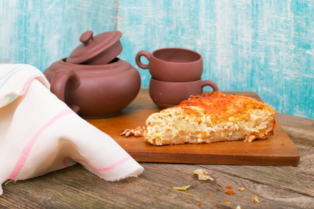 habitual: Badly being pro-concerned pie against the background of ceramic ware. Pie from puff pastry with onions, on a table from old gray boards, lies a kitchen towel nearby. Rural style.
