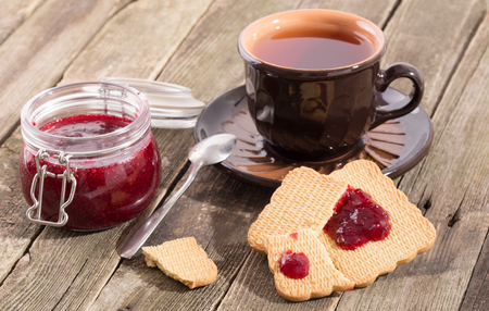 Tea drinking with red berries jam and cookies. The ceramic cup with tea costs on a table from old boards, the jar of jam and pieces of cookies smeared with jam nearby