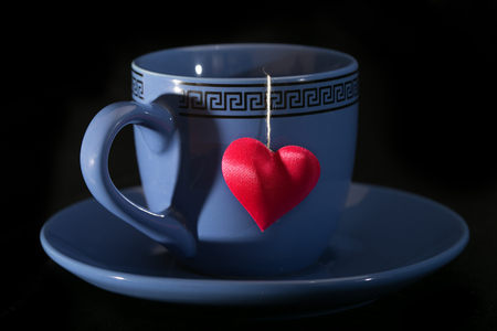 reflection of life: Cup with a shadow in the form of heart and a heart on a thread. A cup on a saucer, a red heart from a tea bag, a black background