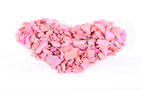 Heart from pink stones on white boards. The heart is laid out from small pink stones on the boards painted with white paint