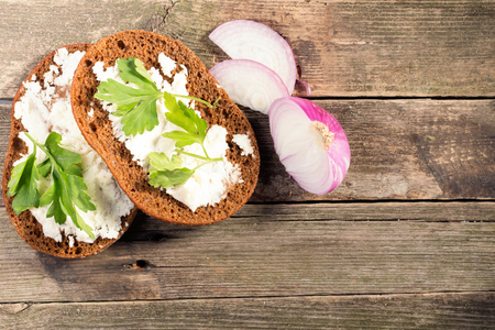 Rye bread with soft cheese and greens. Composition in rural style, white ware on a white wooden table. The food lies on a napkin from fabric. Selective focus