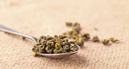 Dry leaves of green tea and teaspoon. A light background from sacking, a close up, selective focus. Grade milk oolong tea