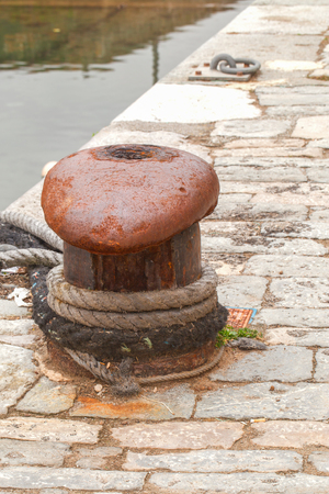 Bollard by corrosion defect. Аround bollard is tied a rope. The mooring is laid out by a stone blocks