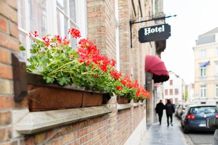 ortseingangsschild: Errichtendes Fragment des Hotels in Brügge. Die alte europäische Stadt, das Backsteinbau, an den Fensterschachteln mit roten Farben. In der Ferne vage ein Straßenfragment mit Passanten und Autos. Selektiver Fokus, der größte Teil eines Schusses ist es verwaschen