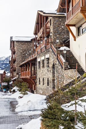 SOLDEU, ANDORRA - FEBRUARY 7, 2017: Street of Soldeu ski resort in the winter. Houses from a stone, wet asphalt, in the distance the mountains covered with snow 報道画像