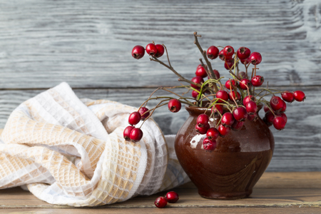 Hawthorn in a ceramic pot, rural style. Red berries of a hawthorn in a brown clay vase, nearby a kitchen towel