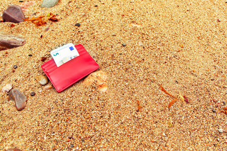 The lost purse on the seashore. The sandy beach, a small red purse with the note of five euros