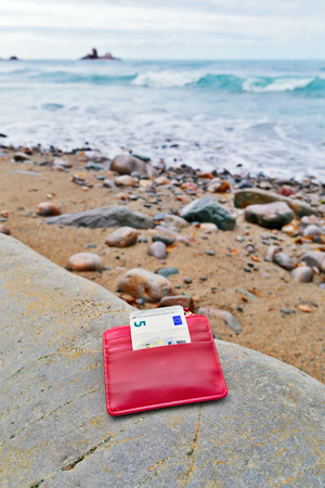 The lost purse on the seashore. The stony beach, a small red purse with the note of five euros Stok Fotoğraf